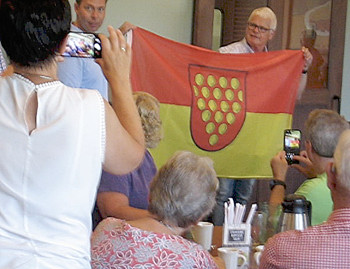 Photograph of a flag being presented to the Bentheimers International Society by tourists from Grafschaft Bentheim