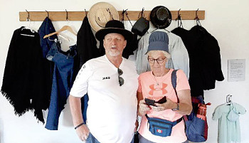 Photograph of two members of the tour group from Grafschaft Bentheim trying out Amish headwear