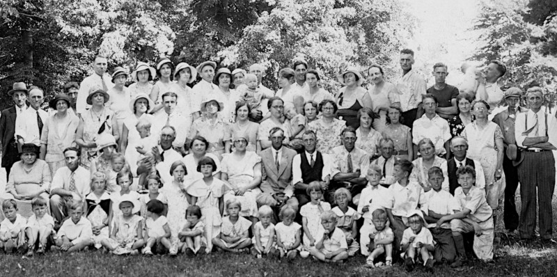 Black and white photo of around 100 people at a family reunion in the 1930s.