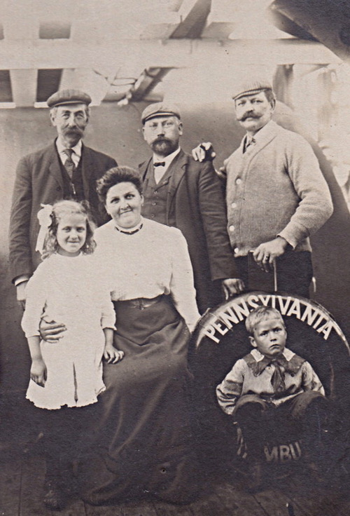 Four adults and two children on board a ship with a life ring reading Pennsylvania