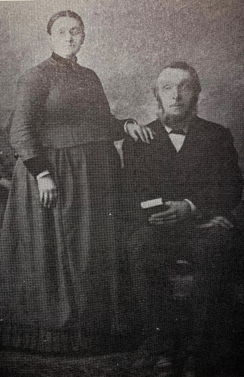 Black and white photo of a woman standing next to her seated husband