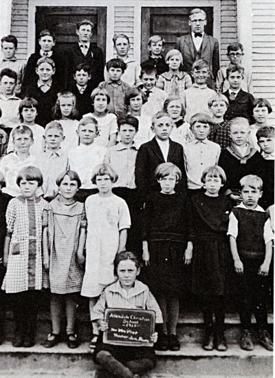 Photo of children standing in front of a school in 1928.