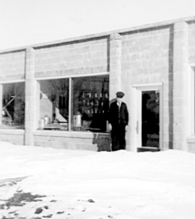 Photo of man in winter standing outside door of a new concrete block hardware store.