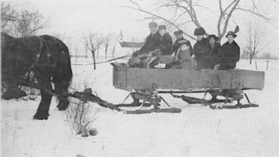 Photo of a family of seven in an old wooden sleigh, which is being pulled by one horse. A church is in the far background.