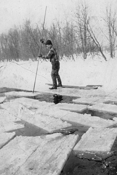 Photo of man on frozen-over river, pushing cut-out sections of ice with an ice hook.