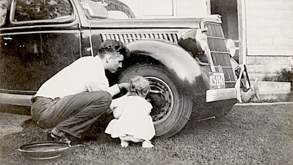 Black and white photo of a toddler in white dress helping her father change a tire, ca. 1942.