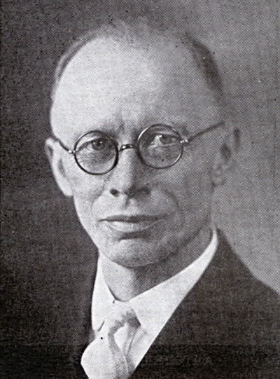 Photo of Rev. Keegstra, wearing round eyeglasses, white shirt and tie, and black suitcoat.