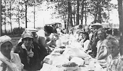 Photo of people sitting at a long picnic table in the woods.