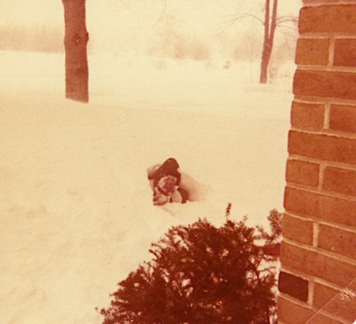 Photo of a child playing in the snow. Most of her body is inside a snowdrift, with only her head sticking out.