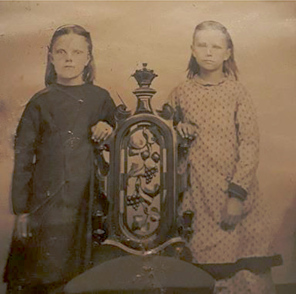 Photo of two young girls posing by a chair.