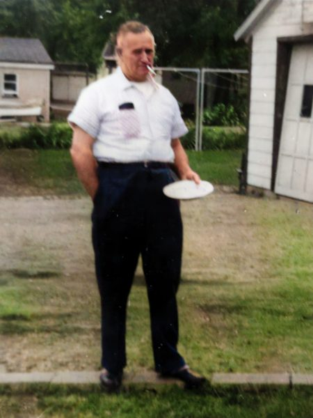 Photo of Albert Kortmann with a Frisbee and smoking a pipe in his backyard.