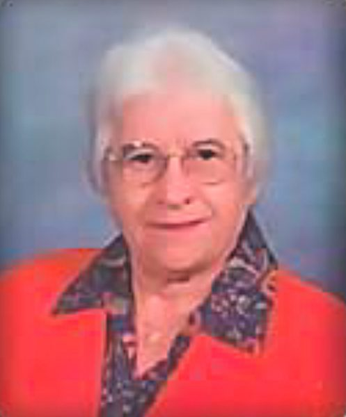 Color photo of Nancy Chapel wearing a print blouse and red jacket