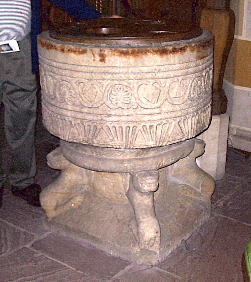 Photo of a sandstone baptismal font engraved with a pattern on top and with four faces at each corner of the base.