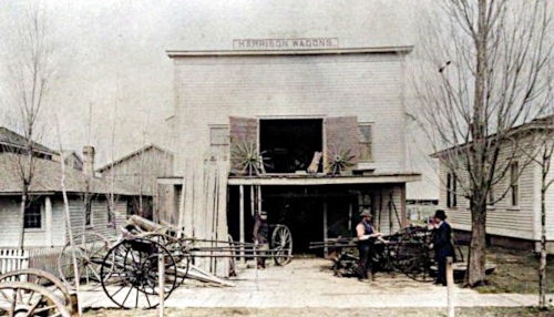 """Photo of the blacksmith's shop in Graafschap. A sign above the building reads, """"Harrison Wagons."""""""