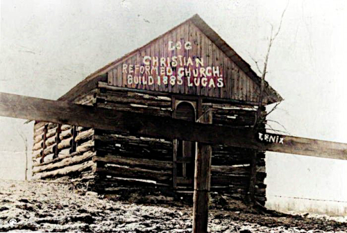"""Log cabin building of the Lucas Christian Reformed Church. Writing on the photo reads, """"Log Christian Reformed Church building 1883 Lucas."""""""
