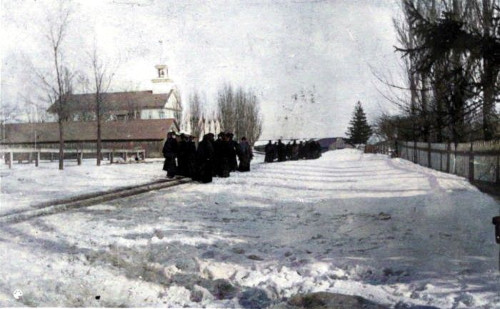 Photo of a group of people walking along a path in winter. In the distance on their left are the church stables, and the Graafschap Christian Reformed Church's steeple and roof can be seen behind the stables.