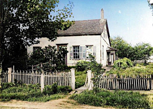 Photo of a wooden house with windows and shutters, a picket fence in front with a broken gate, and long grass in the yard.